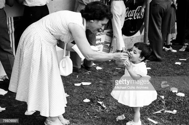 Woman helps a young fan with a snack at the American Jazz Festival in July 1958 in Newport, Rhode Island.
