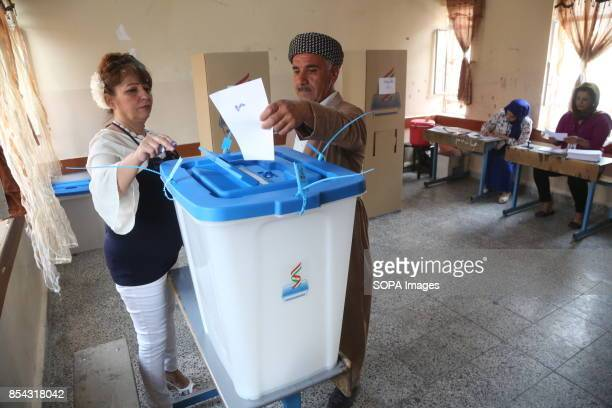 A woman helps an old man to put his vote at the voting station September 25 2017 is a historic day for Kurdish people around the world as many...