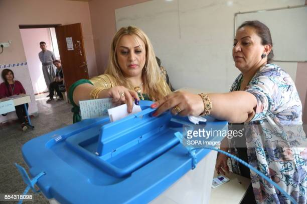 A woman helps another to cast her vote at the voting station September 25 2017 is a historic day for Kurdish people around the world as many Kurdish...