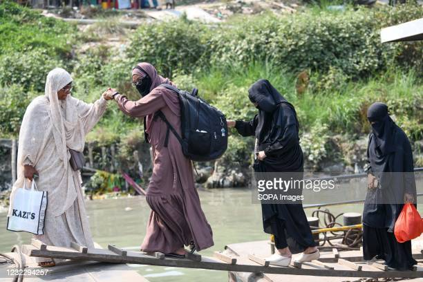 Woman helps another walk on a bridge to the speed boat as they return home from Dhaka before lockdown at Mawa Ferry terminal near Dhaka. Bangladesh...