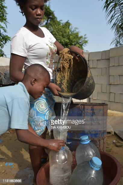 A woman helps children to fill their bottles with the water of the well in the popular district of Yopougon where inhabitants lack of of drinking...