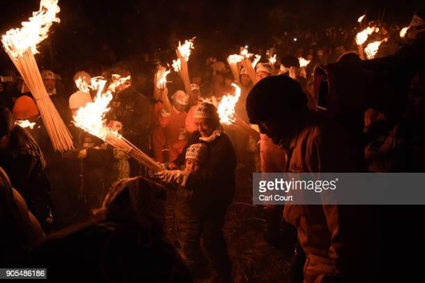 A woman helps her child carry a flaming stick during the Nozawaonsen Dosojin Fire Festival on January 15 2018 in Nozawaonsen Japan The festival is...