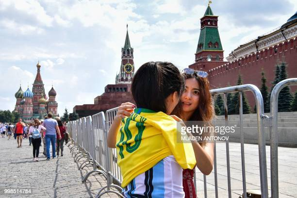 A woman helps her friend to put on a jersey of Brazil's forward Neymar over a jersey of Argentina's forward Lionel Messi as they visit Red Square in...