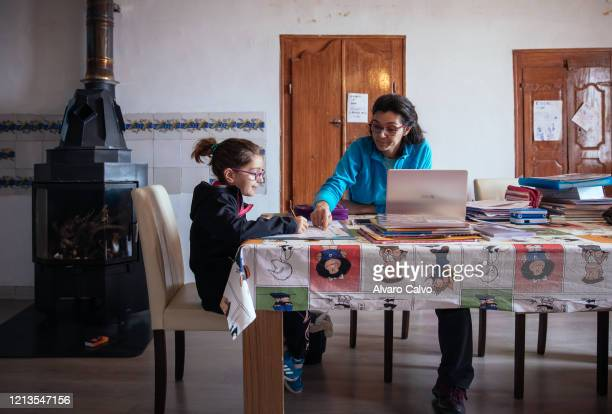 A woman helps her young daughter to do their homework while they are confined to their home in a city of 13 habitants on March 19 2020 in Santa...