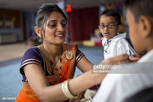 A woman helps to dress a young member of the Shree Muktajeevan Pipe Band before a visit by Mayor of London Boris Johnson at the Shree Swaminarayan...