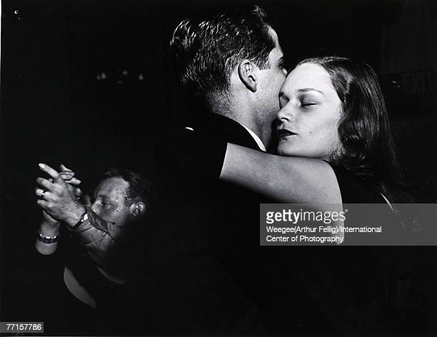 A woman her eyes closed dances with her gloved arms around the neck of a man in Times Square in the early morning New York New York 14th August 1945...