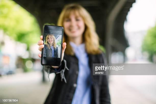 vrouw haar portret op haar telefoon - tonen stockfoto's en -beelden
