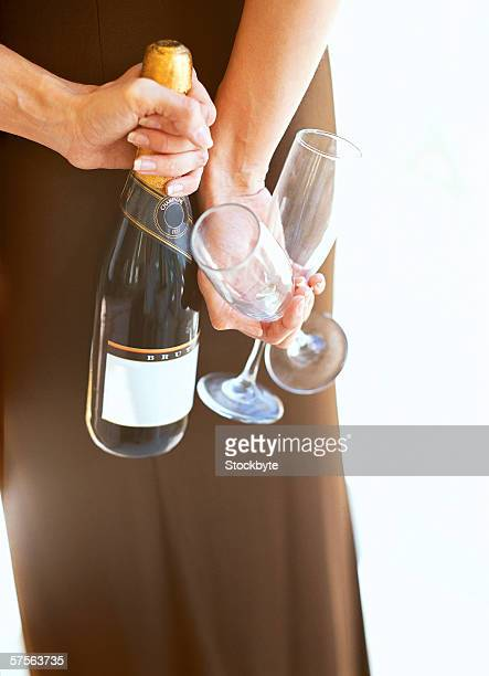 woman hiding a bottle of champagne and two glasses behind her back
