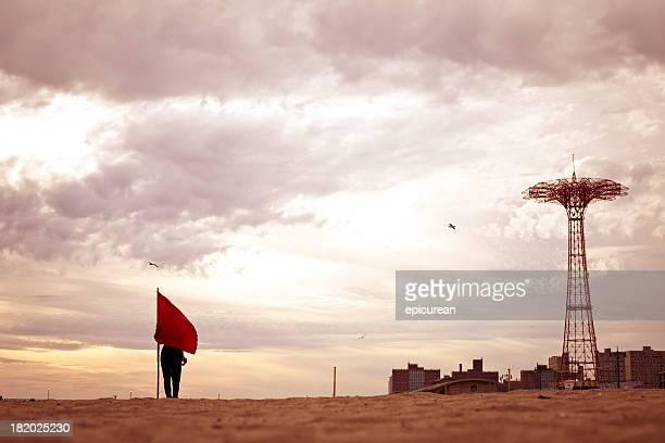 woman hiding behind a flag on coney island - landelement stockfoto's en -beelden