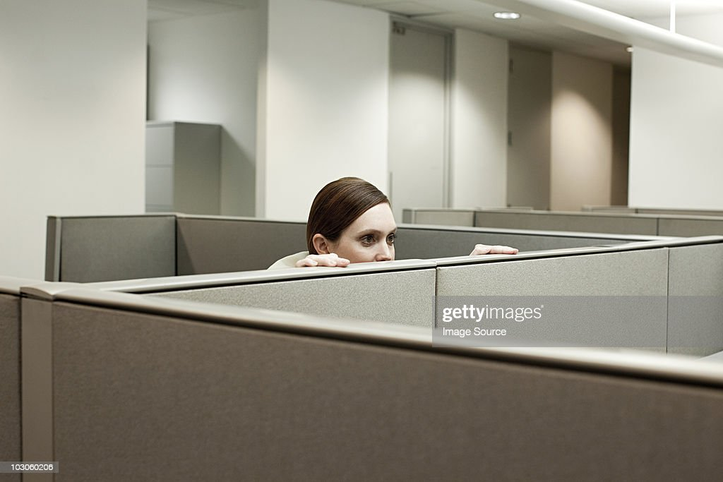 Woman hiding behind cubicle in office : Stock Photo