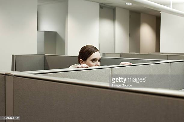 woman hiding behind cubicle in office - conspiracy stock pictures, royalty-free photos & images
