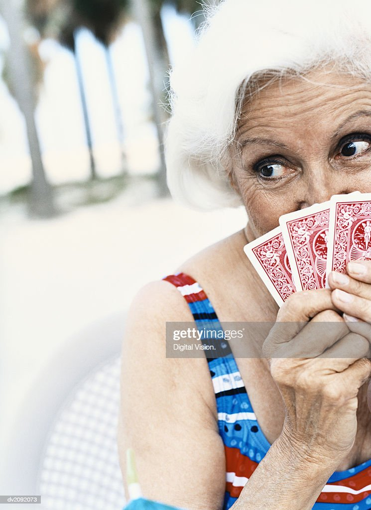 Woman Hiding Behind Her Playing Cards : Stock Photo
