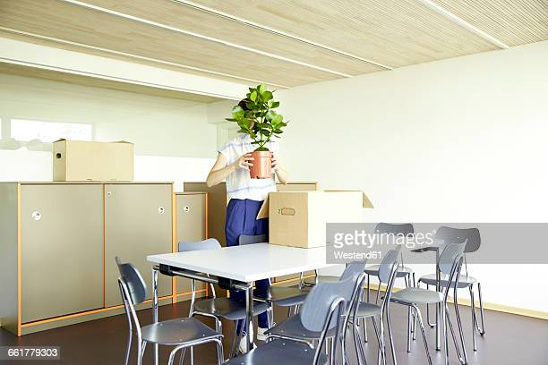 Woman hiding behind potted plant in new office