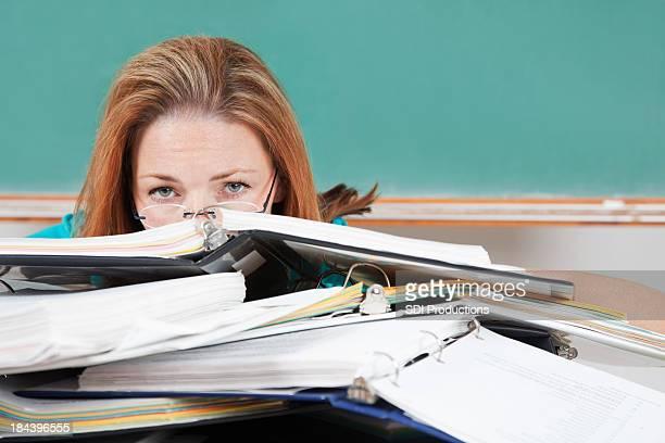 Woman hiding behind school binders in classroom