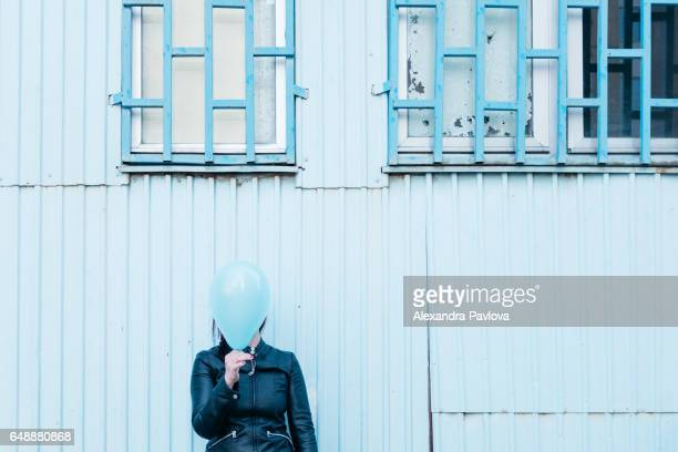 Woman hiding face behind blue balloon, against blue background