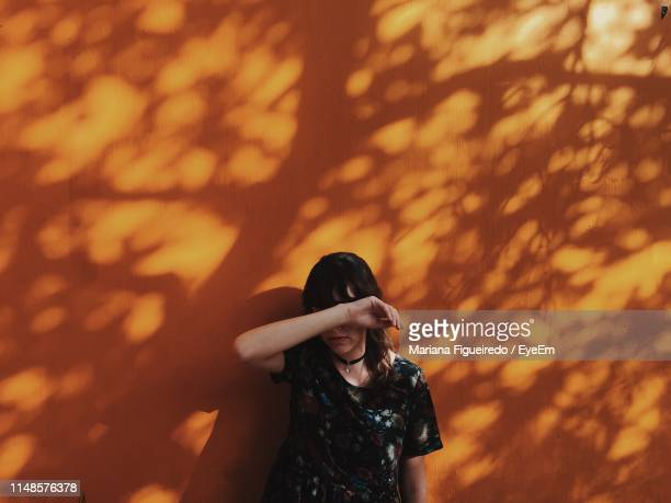 woman hiding face with hand while standing against orange wall - una sola mujer joven fotografías e imágenes de stock