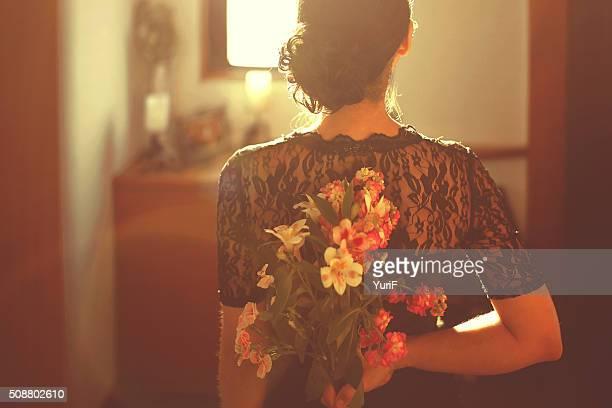 Woman hiding flower
