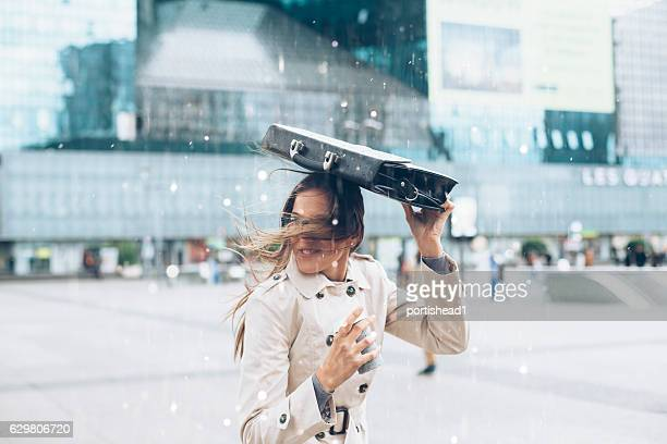 Woman hiding from the rain with business bag