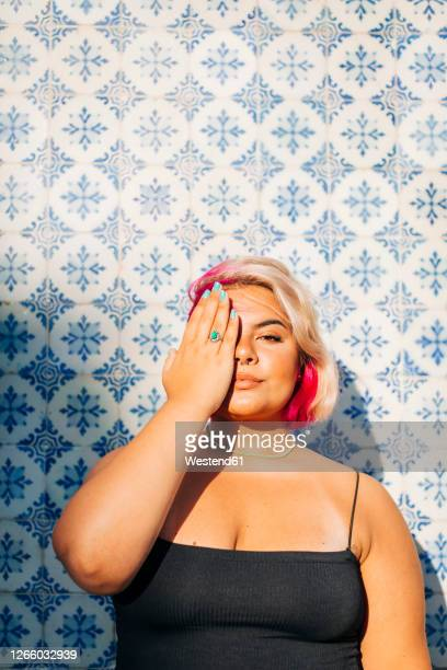 woman hiding half face with one hand against patterned wall - femme grosse photos et images de collection