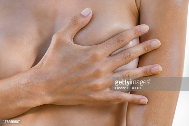 woman hiding her breast with her hand - nackte frau brüste stock-fotos und bilder