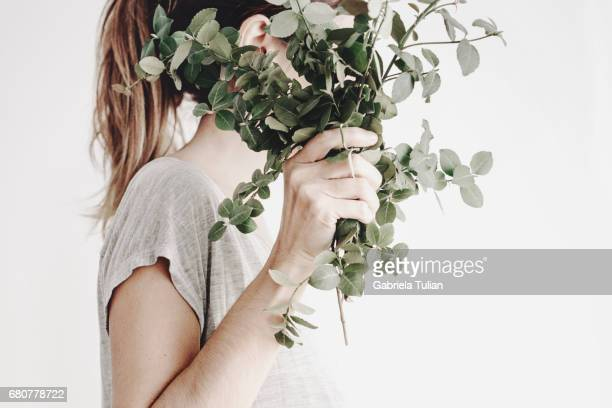 Woman hiding her face with a plant bouquet