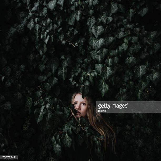 Woman hiding in an ivy bush