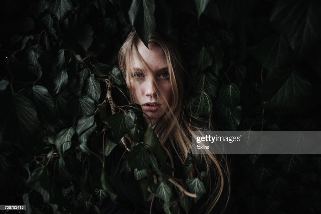 Woman hiding in an ivy bush : Stock Photo