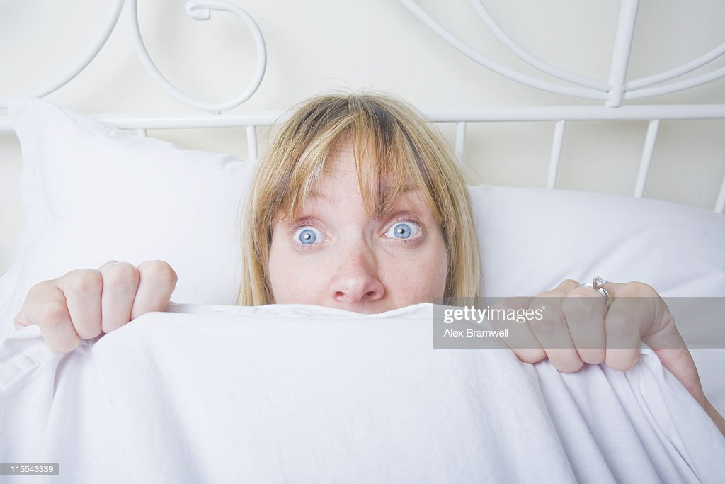 Woman hiding in bed : Stock Photo