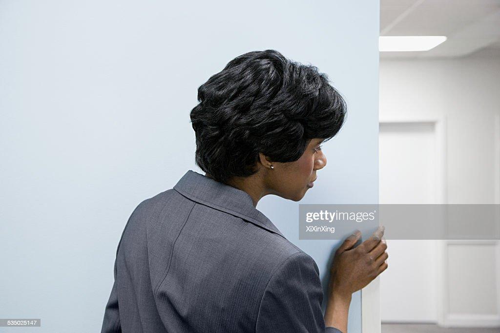 Woman hiding peering round corner : Stock Photo