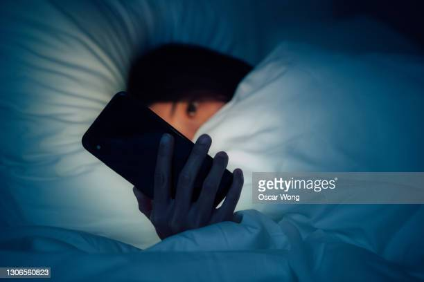 woman hiding under the blanketed and using smart phone at late night on bed - unrecognisable person stock pictures, royalty-free photos & images