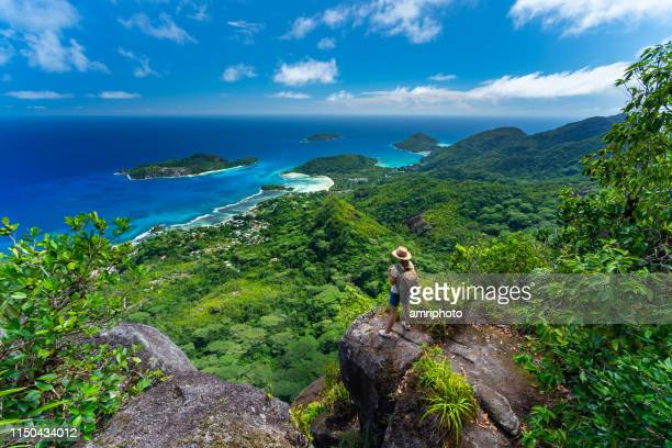 woman high above on tropical island mountain - seychelles stock pictures, royalty-free photos & images