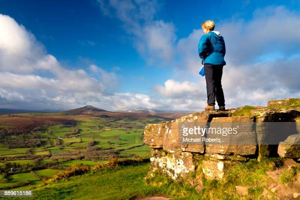 Woman hiker enjoying the view towards Sugar Loaf (Mynydd Pen y Fal) from Skirrid in the Black Mountains, Brecon Beacons national park, Wales