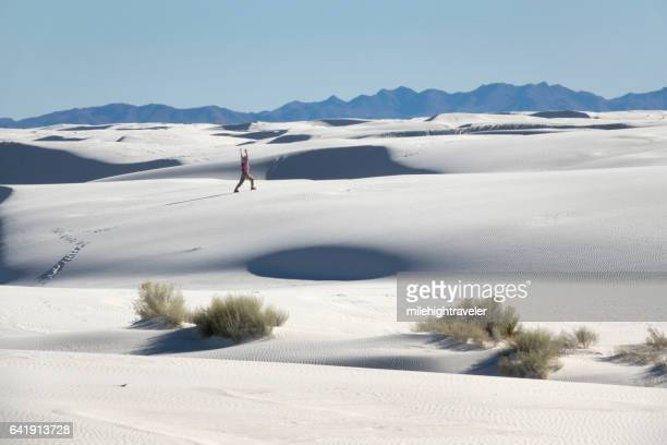 woman hiker explores white sands new mexico yoga stretch mountains - milehightraveler stock pictures, royalty-free photos & images