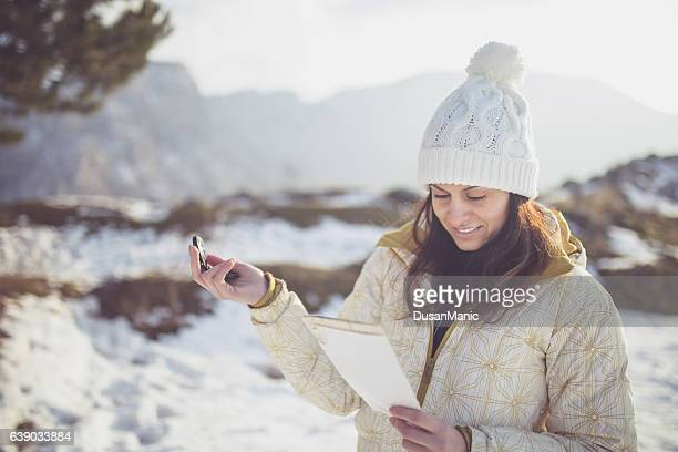 Woman hiker reading map in mountains on hiking trip.