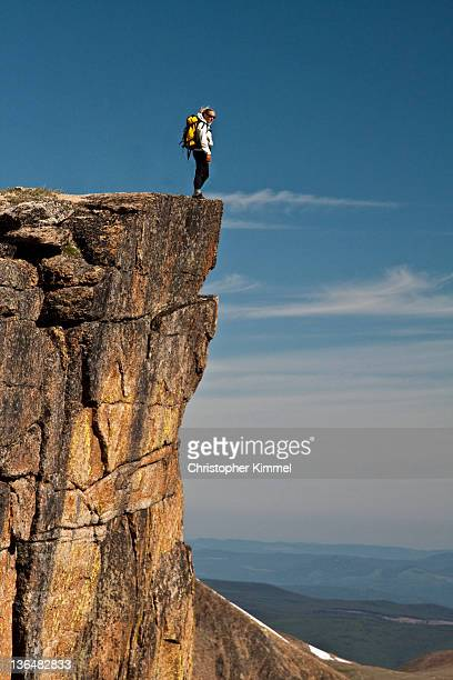 Woman hiker standing on cliff edge