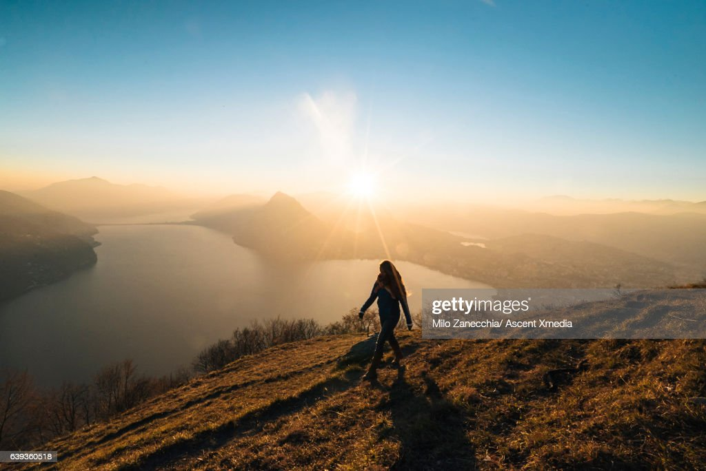 Woman hikes along trail above lake, valley : Stock Photo