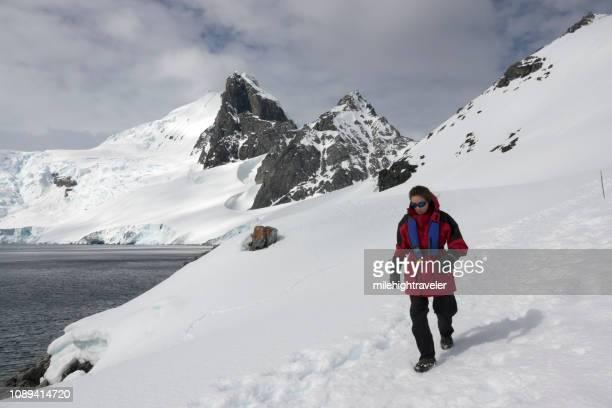 Woman hikes Antarctic Peninsula mountain Orne Harbour Gerlache Strait Antarctica