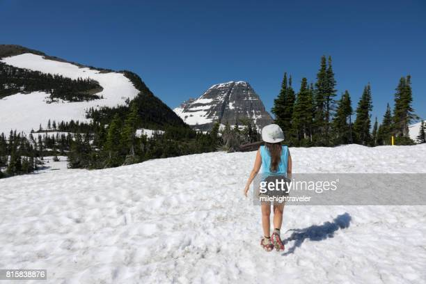Woman hikes Glacier National Park Logan Pass snowfield Bearhat Mountain Montana
