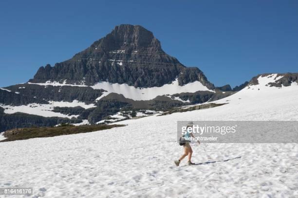 Woman hikes Glacier National Park Logan Pass snowfield Reynolds Mountain Montana