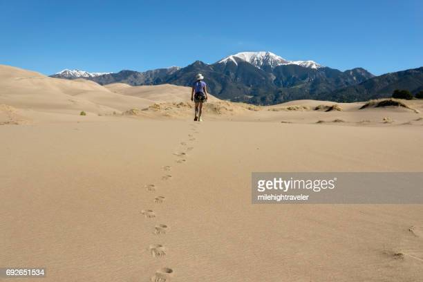 woman hikes great sand dunes national park sangre de cristo mountains colorado - great sand dunes national park stock pictures, royalty-free photos & images