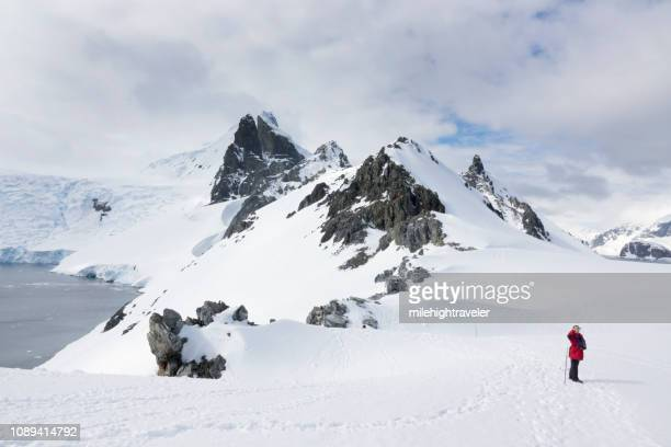 Woman hikes takes photo Antarctic Peninsula mountain Orne Harbour Gerlache Strait Antarctica