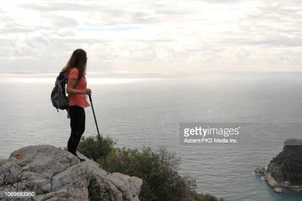 Woman hikes to promontory above sea, coastline