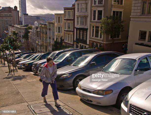 A woman hikes up the steep hill at the corner of Mason and California Streets on December 22 in San Francisco California Despite cold and rainy...