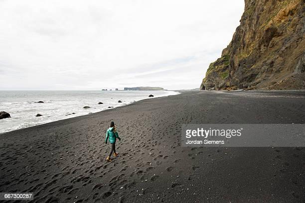 A woman hiking a black sand beach.