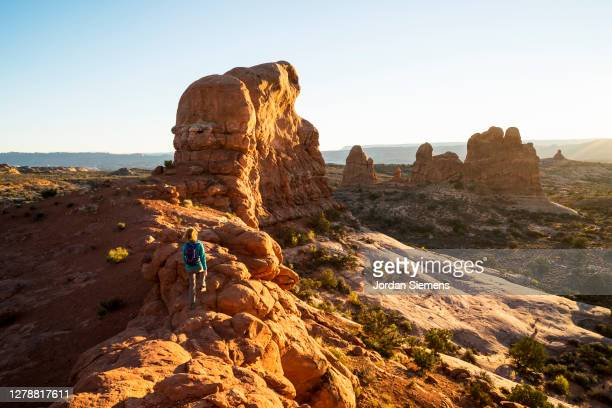 a woman hiking a scenic trail in arches national park. - アーチーズ国立公園 ストックフォトと画像