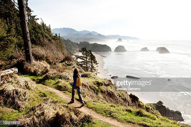 a woman hiking a secluded path along the coastline. - pacific ocean stock photos and pictures