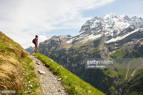 A woman hiking a trail in the Alps