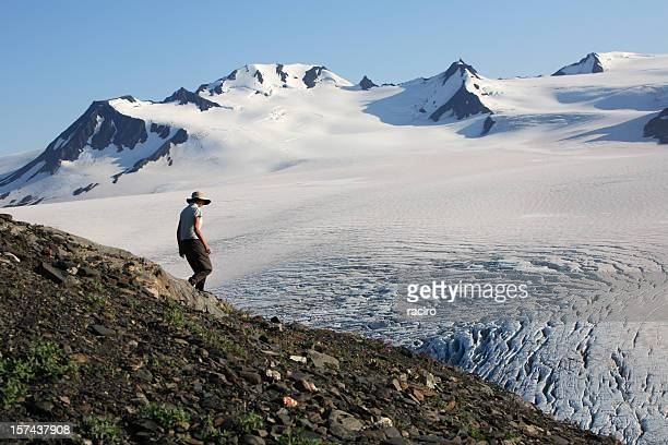woman hiking above a large snow field and gracier.