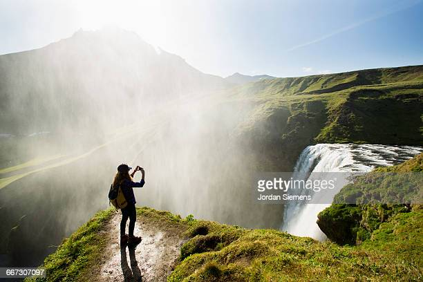 A woman hiking above a waterfall.