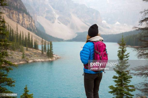 a woman hiking above lake moraine near banff. - ショッキングピンク ストックフォトと画像